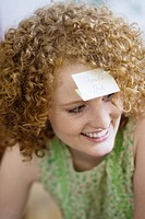 Redheaded woman with sticky notepaper on forehead