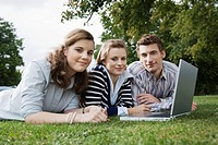Students using laptop in grass (thumbnail)