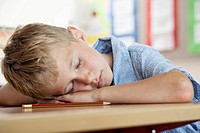 Boy sleeping on desk in classroom