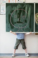 Boy holding blackboard with smiley face drawing