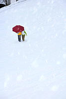 Couple walking through snow together holding umbrella