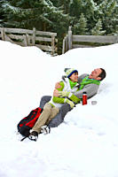 Laughing couple drinking from thermos and laying in snow together