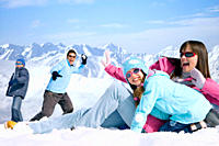 Laughing family having snowball fight together on mountain top