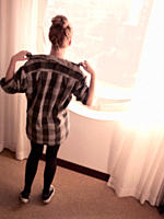 Rear View of Young Woman in Checkered Shirt Looking Out Window