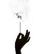 Silhouetted Hand Holding Smoking Incense on White