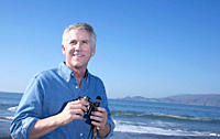 USA, California, Fairfax, Mature man with binoculars on beach