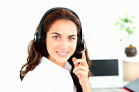 Pretty hispanic businesswoman with headset sitting at her desk in a call center