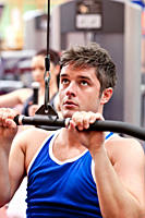 Muscular male athlete practicing body_building in a fitness center