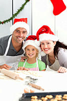 Cheerful family kneading biscuits for Christmas standing in the kitchen