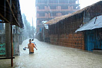 A man wades through flood water at a community in Chittagong city Bangladesh November 6, 2007