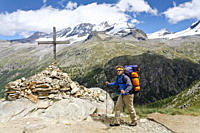 Hiker near summit cross, Croix de la Roley, Gran Paradiso in background, Valsavarenche, Gran Paradiso National Park, Aosta valley, Italy