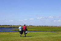 Golf players on Falsterbo golf court with little beach huts in the background, Falsterbo, Skanoer, Skane, South Sweden, Sweden