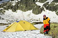 Mountaineer next to the yellow tent in the Sierra de Béjar Natural Park, in Salamanca province, Biosphere Reserve of Sierra de Béjar and Francia