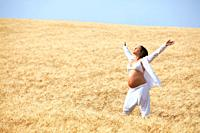 Pregnant woman relaxing in field