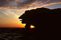 Setting sun through rock arch Puerto Egas, Isla Santiago, Galapagos Islands, Ecuador
