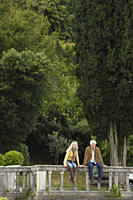 Senior couple sitting on railing in front of trees, Italy