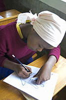 Christian schoolgirl working at school, Ndogo Primary School, Rift Valley, Kenya, East Africa, Africa