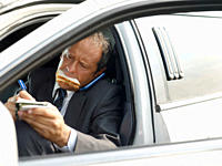 Driver eating sandwich on limousine