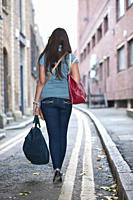 Young female walking in street with bag