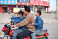A father and two sons on a motorbike in Xian city, northern china, none of whom are wearing crash helmets