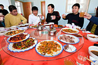 Chinese people sit down for a meal in a restaurant which includes several dishes of dog meat