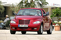 Car, Chrysler PT Cruiser Convertible 2.4 Limited, Cabrio, model year 2004_, ruby colored, open top, standing, upholding, diagonal from the front, fron...