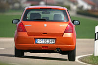 Car, Suzuki Swift 1.3, model year 2005_, orange , Limousine, small approx., driving, diagonal from the back, rear view, country road