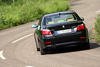 BMW 550i, model year 2005_, black, driving, diagonal from the back, rear view, country road