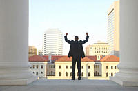 African American businessman with arms raised at courthouse