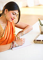 Mixed race woman in traditional Indian clothing writing in notebook