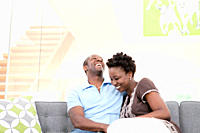 Laughing couple sitting on sofa in living room