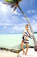Caucasian woman standing on beach near tropical ocean (thumbnail)
