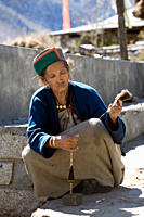 traditionally dressed elderly Kinnauri Buddhist Indian woman concentrating on spinning yarn, Chitkul, Kinnaur valley / district, Himachal Pradesh, Him...