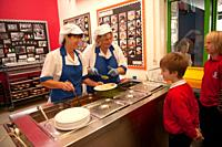 Dinner ladies serving lunch in a primary school canteen, Wales UK