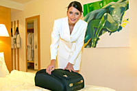 Woman unpacking suitcase in hotel