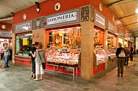 Delicatessen shop Butcher's and customers and the famous spanish hams Triana Market place Sevilla Andalucia Spain