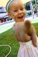A happy 3 years old girl with face painting pointing to the camera