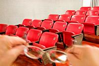 Man holding his glasses in an auditorium