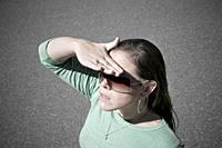 Young woman, wearing sunglasses, blocking the sun with her hand