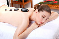 Woman having a hot stone treatment, eyes closed