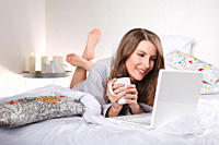 Woman lying on bed with laptop, smiling