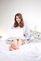 Woman sitting on bed and using laptop, smiling