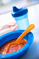 Baby food in bowl with baby bottle in background