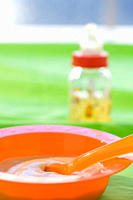 Baby food in bowl with baby bottle in background (thumbnail)