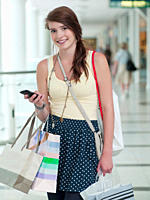 Teenage girl with cell phone carrying shopping bags in mall