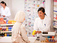 Pharmacist handing medication to customer in drug store