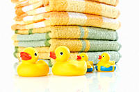 Close up of rubber ducks with stack of towels in background