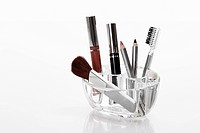Variety of cosmetics in rack against white background