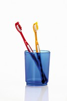 Toothbrushes in toothbrush holder on white background