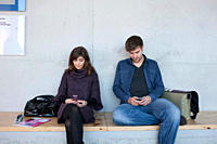 Germany, Leipzig, University students sitting and using mobile phone